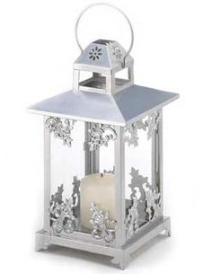 "Silver Scrollwork Candle   Holder Lantern    Decorative lantern in gleaming   silver finish and graceful scrollwork   for an elegant candle lantern.  Also   use as an artistic display for small   houseplant or mini figurine.  Handle   at top for hanging. Iron and glass.   Candle not included.   7 1/4"" square x 15 1/2""H    #339891    $29.00"