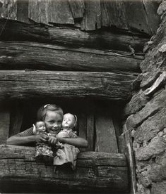 William Eugene Smith It Nice the way the little girl popped out of the window to get a picture with her natural smile it great the way it in black and white because you can see all the dark and light areas are.