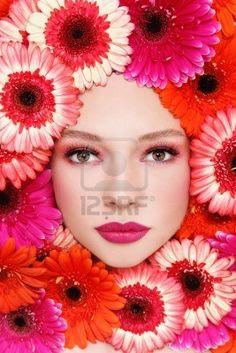 彼女の顔の周りでスタイリッシュなメイクアップと鮮やかな花と美しい女性の肖像 ストックフォト
