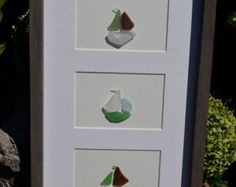 This gorgeous frame is truly One of A Kind! 4 beachglass/seaglass sail boats would put a smile on any sailors face. Awesome piece of nautical decor. All pieces of glass were hand gathered by me on the shores of either Lake Huron or Lake Ontario in Canada. This gem is larger than most of my framed pieces measuring approx 31.5 x 9.5 . It has hooks on the back for hanging. Thanks for stopping by my store, Enjoy! If you would like a similar piece but different size, feel free to contact me