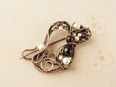 Brooch made of copper, pearl and garnet.