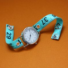 """The watch band is repurposed from a vinyl measuring tape and closes securely with a silver colored snap. The band is adjustable by simply snapping into the next closure. The round watch face is a brand new Geneva quartz and stainless steel watch with a pearlized face. The watch band has two snaps to fit at 7.5"""" (19.1 cm) and 8"""" (20.3 cm) around."""