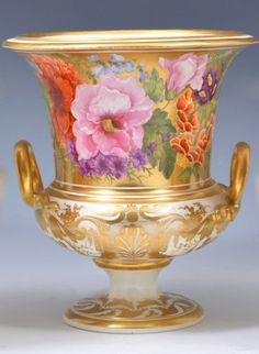 "A Derby porcelain campana vase, painted by William ""Quaker"" Pegg, 1810-20, panoramically painted, with life-size flowers, including roses and violets and primulas, against a gilt ground, gilt serpent handles, the bowl with gilt decoration, gilt decorated circular foot, standard red mark and numbered 36, 20cms."
