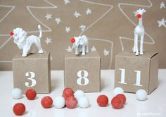 DIY Advent Calendar for the holiday for those of you who does it. Cute little animal statues/toys painted white and their noses glued with red poms. Simple white stencils on kraft boxes.
