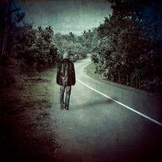 Man walking down an empty road in a tropical rural landscape