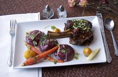 ... Braised Lamb Shank, Goat Cheese Beet Ravioli & Confit Root Vegetables