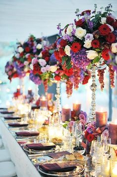 Opulent centerpieces of red, white and purple roses, purple hydrangeas and dangling grapes make a bold statement.