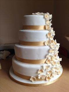 White and gold wedding cake with cascading flowers and butterflies