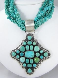 """Sterling Silver Carico Lake & Sleeping Beauty Turquoise Bead Necklace  Carico Lake turquoise gems are in this pendant on five strands of Sleeping Beauty turquoise nuggets by Ray Bennett, Navajo. The gems are set in smooth bezels spaced with silver beads and hand stamped designs at the outer edges. The pendant is 2 7/8"""" by 3"""". The beads have a hook and clasp closure and are 25"""" in length. Signed by the artist.   Price: $995.00"""
