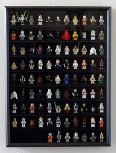 LEGO Minifigure Display Cases -- Basic shadow box with thin wood slats cut to fit and stacked Lego bricks as supports....My 'COLLECTION Collector' Kiddo NEEDS THIS!
