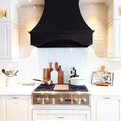 White kitchen + black range hood looks absolutely amazing & is so different from most kitchens! - totally loving this 'look! Kitchen Hoods, Kitchen Stove, New Kitchen, Kitchen Decor, Kitchen Cabinets, Black Kitchens, Cool Kitchens, Kitchen Black, Dream Kitchens