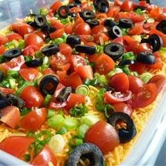 Seven Layer Tex Mex Dip | This is a great, easy recipe people love. Our family has made it for gatherings for as long as I can remember. Refried beans are layered with guacamole, a seasoned sour cream mixture, cheese and vegetables. Serve it with tortilla chips. Enjoy!
