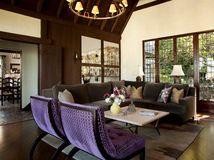 Tudor style wood beams, windows, purple side chairs, barn doors.