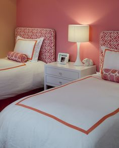 girl's rooms - pink accent wall pink geometric fab ric upholstered twin headboards white nightstand white lamp pink bolster pillows white lamp white hotel bedding pink frame