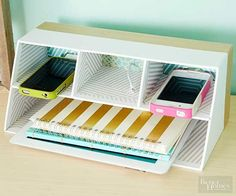 This freebie charging station is a repurposed cardboard desk organizer -- the kind you use for pencils and notepads. Turn it on its side, and use a sharp crafts knife to cut holes for cords. Decorate with paint and washi tape.