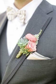 a grey suit with a pink and succulent boutonniere