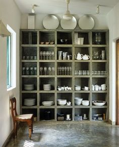 Waxed concrete floor.. raw wood shelving - but truly talented arrangement