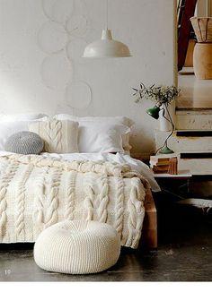 1. Op een bed hoort minstens één gebreid plaid en dan het liefst – zoals hier – aangevuld met grof gebreide kussens. Ik heb al tijden een obsessie voor gebreide poefjes die je hier ook op de foto ziet. Misschien ga ik er ooit één zelf breien; in de winkel zijn ze namelijk peperduur.
