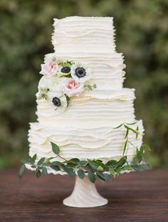 White ruffled wedding cake with flowers and leaves at the base.