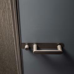 un dettaglio dello stipite slim, profilo strutturale e maniglia in alluminio brown, vetro laccato opaco grigio ardesia