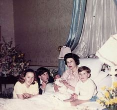 Queen Elizabeth II shortly after giving birth to Prince Edward, surrounded by her sons Charles and Andrew and her daughter Anne, 1964
