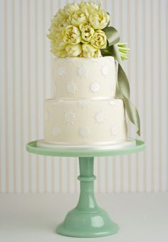 Oversize polka dots and a miniature, fresh floral bouquet on the top tier (as opposed to a typical cake topper) makes this wedding cake stand out. Cake by Peggy Porschen.