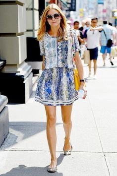 Olivia Palermo wears a printed short sleeve dress, python printed flats, yellow bag and sunglasses.