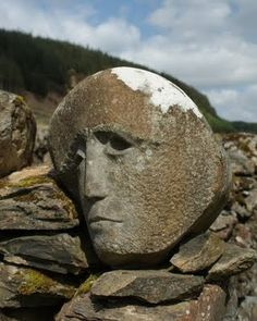 """Ancient and Bold """"Celtic Face"""" resting in a stone fence, used as a land boundary marker -- Galloway Forest Park, Scotland."""