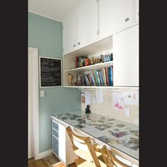 The desktop is a sheet of glass over postcards and family photographs.