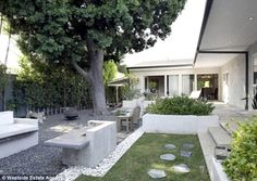 Modern courtyard: The outside space is equally minimalistic, with white and grey gravel, white stone benches and stepping stones