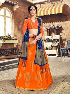 A vibrant orange Banarasi silk lehenga choli ensemble for a grand daytime celebration! The orange Banarasi silk lehenga choli is detailed with bold shimmery forms and is paired with a blue ornate Banarasi silk dupatta. Accessorize this Banarasi silk lehen Lehenga Choli Latest, Orange Lehenga, Banarasi Lehenga, Ghagra Choli, Lehenga Choli Online, Bridal Lehenga Choli, Silk Dupatta, Patiala Salwar, Anarkali