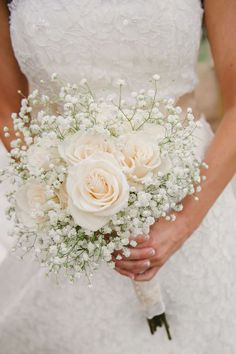 A simple bouquet of ivory roses and baby's breath. Photo via Project Wedding More #howmuchdoweddingflowerscost