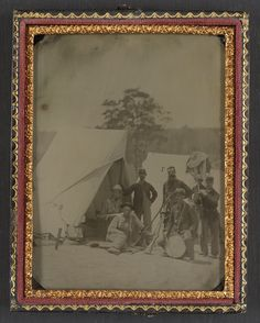 Seven unidentified soldiers in Union uniforms with drum and stacked rifles in front of tent