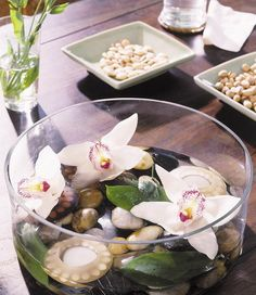 10 - Flowers and pebbles inside a glass bow placed as a table centerpiece