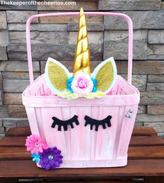 Unicorn Easter Basket Materials: Pink or white basket with handle (found the one used at a local Walmart) Unicorn horn (find one like what I used HERE) (Find more like it HERE) Black craft felt Scissors Glue Gems Flowers Easter basket filler HERE Directions Glue Unicorn horn and ears to the top, front side of the basket Cut eyes out of craft felt and glue on just below horn Glue on additional flowers and gems onto basket Fill basket with basket filler Add gift items into basket ITEMS…