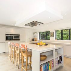 Open plan kitchen, shades of white, colour bar stools and cooking books.