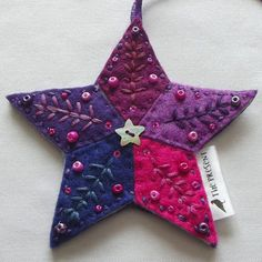 Felt Star Decoration, entirely hand cut and stitched. 5 diamond shapes in 5 shades of purple and pink felt, stitched onto a purple felt backing, with an additional layer of thick felt inside to give it body. Embroidered in 5 different complementary shades of purple and pink thread,