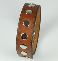 "This brown men's leather bracelet is 3/4"" wide with evenly spaced rivets. A single snap closure to clasp and professionally sealed and treated edges provide a long life to a great bracelet. Light brow"
