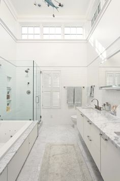 Really big white bathroom.  glassed in shower and plantation shutters on the window.