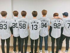 BTS prepping for their first pitch at the Hanshin Tigers Baseball Game by taking pictures with the mascot!