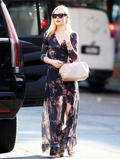Kate Bosworth in a flowing wrap navy dress with pink floral design and lace up heeled sandals.