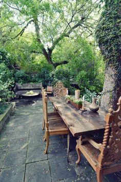 outdoor room - how I love these serious wooden carved chairs at the magnificent long wooden table with charming paving and surrounded by TREES what a fabulous courtyard