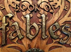 """Fate was well acquainted with how the enormous sign was made to look like a book, with its elaborate oak tree carved in relief on the wooden cover. She moved to the side, looking at the pages pressed tight between the covers, touching them with eager fingers. They were thick, but definitely made of paper. """"It's a real book!"""" she whispered in surprise. [FATE'S FABLES excerpt. traemitchell.com]"""