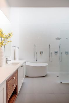 In this modern master bathroom, there's a deep freestanding soaker tub, a dual shower with a glass partition, and a large vanity.