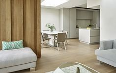 Bright and contemporary open plan kitchen design by Brayer bespoke kitchens. Modern handleless kitchen cabinets with light grey finish. Scandinavian style lounge and dining area with natural oak flooring with light grey tint.