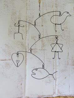 This mobile is made with annealed steel wire and is painted in satin black with Rustoluem paint. It measures about 13 inches tall by 13 inches wide at the widest point. It comes with a snap swivel and 48 inches of jute for hanging. With a fish, a bird, a man, a woman and a heart. Please note that the arms on the wire man will be bent up for shipping and will need to be bent back down from the he-man position to the hug position. International customers please convo me for a shipping price.