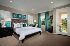 Teal accents pop against a gray headboard in this owner's suite that opens to a private patio. From KB Home. The Whisler Ridge new home community. Lake Forest, CA.