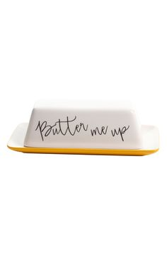 This charming butter dish pairs a sunny yellow base with a clean white lid and playful 'Butter me up' lettering.