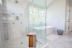 Spa bathroom features a freestanding tub, placed below two windows, placed next to a corner shower clad in grey marble tiles accented with white linear glass tiles lined with stacked corner shower shelves over a marble hex floor.