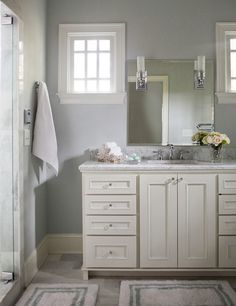 Bathroom Sources. Custom cabinetry is painted Benjamin Moore White Dove. Light fixtures are from Pottery Barn and were installed on top of the mirror. Counter top is Carrara marble. #Bathroom Rachel Oliver Design, LLC.